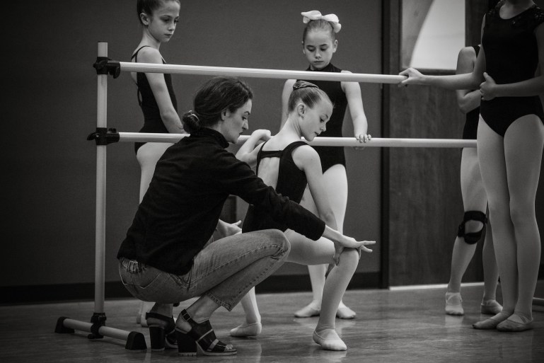 Megan LeCrone squats down to adjust a student's placement. The student, a young woman, is in a grande plie at the barre.
