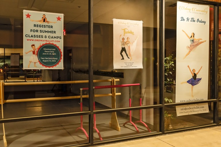Glass windows peering into a dance studio have posters featuring shots of dancers leaping, posing, and more