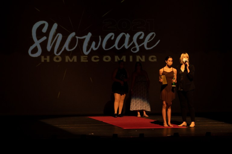 Melanie Gibbs, wearing all black and a mask, holds a microphone onstage, standing next to a teenage student in costume who holds a trophy and a plaque.