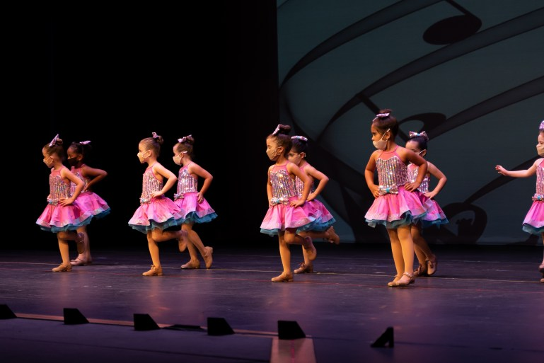 Nine young dancers—around 5 years old—perform a tap dance, wearing glittery tops, pink skirts, bows in their hair, and masks.