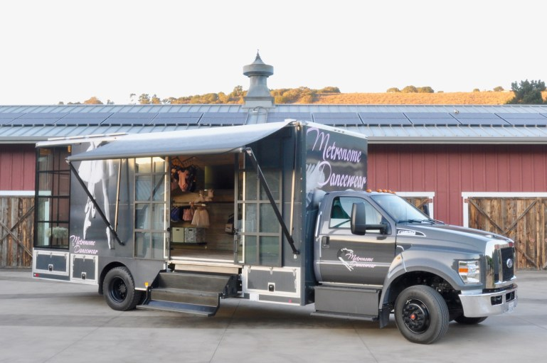 Truck with side lifted up to reveal mobile dance shop of Metronome Dancewear