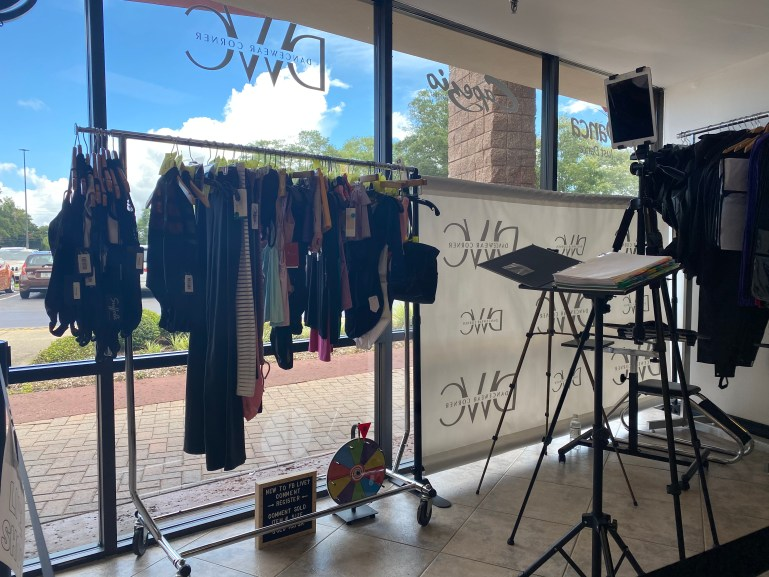Camera and podium with script set up at DanceWear Corner, with front store window in the background and a rack of dancewear.
