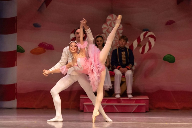 Teen dancers perform a pas de deux in front of a colorful backdrop covered in sweets, and a younger couple of dancers who watch from a candy throne. The young woman, in a pink tutu, is supported in a penche by her male partner, who wears all white.