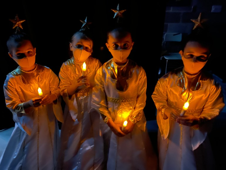 Four young girls are dressed in angel costumes backstage. They have headpieces with stars on them, and hold fake candles. They are all wearing masks.