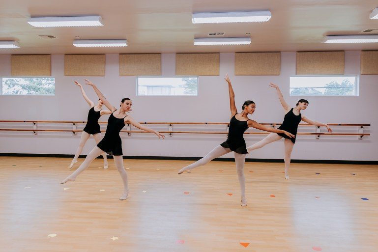 Four teen dancers perform a ballet combination in a bright studio, arms straight and leaning slightly to the side, and leg extended to the opposite side.