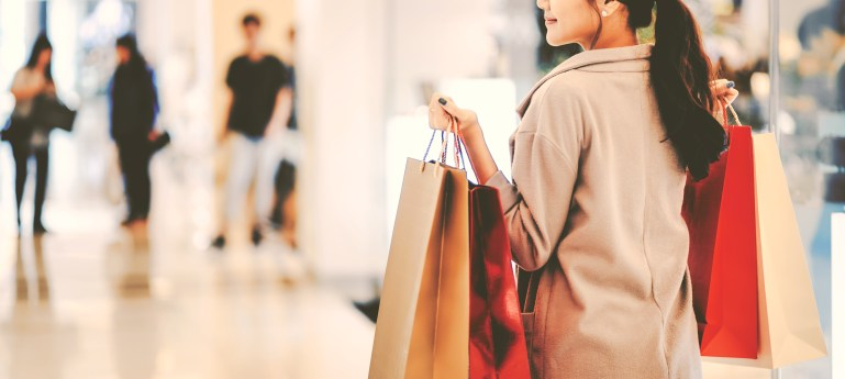 A young woman with dark hair, seen from the back, holds several shopping bags as she walks around a store