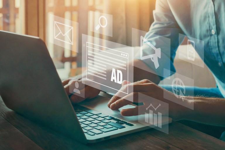 photo illustration of person at computer keyboard looking at digital ads.