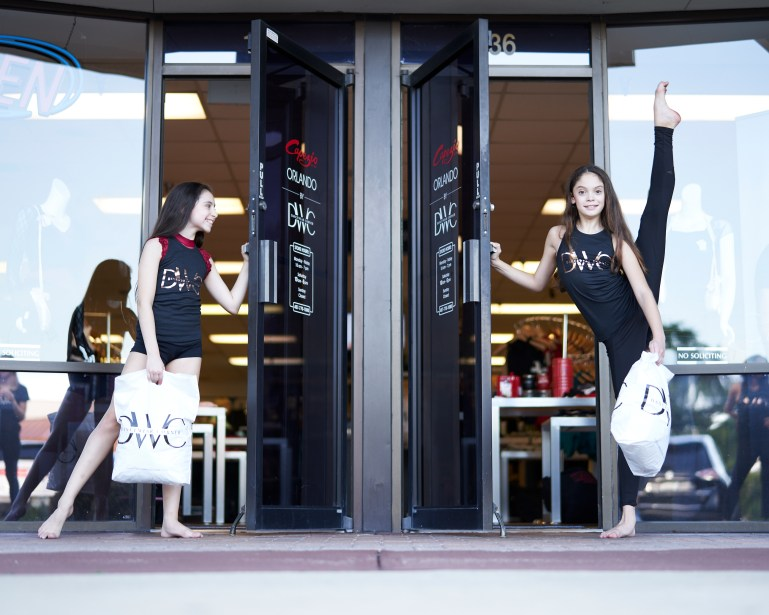 Two young dancers pose outside The DanceWear Corner, wearing the store's merch. One extends her leg to the sky, the other tendus to the side.