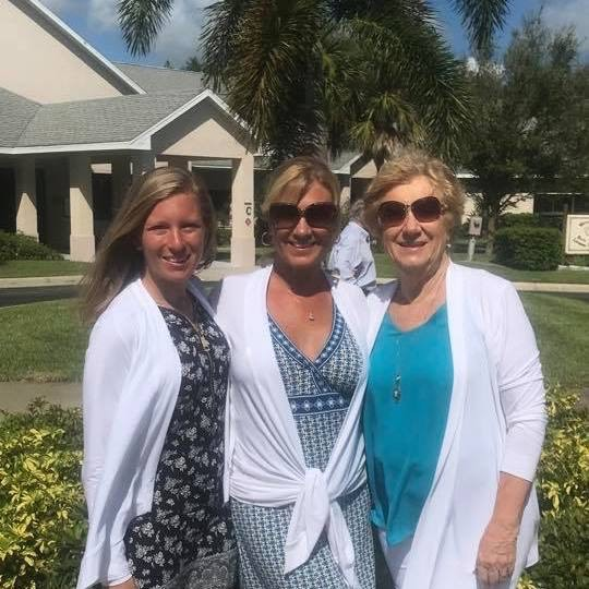 The three women of Kaye-Lynn Dance Studio pose together outside, wearing dresses and white sweaters