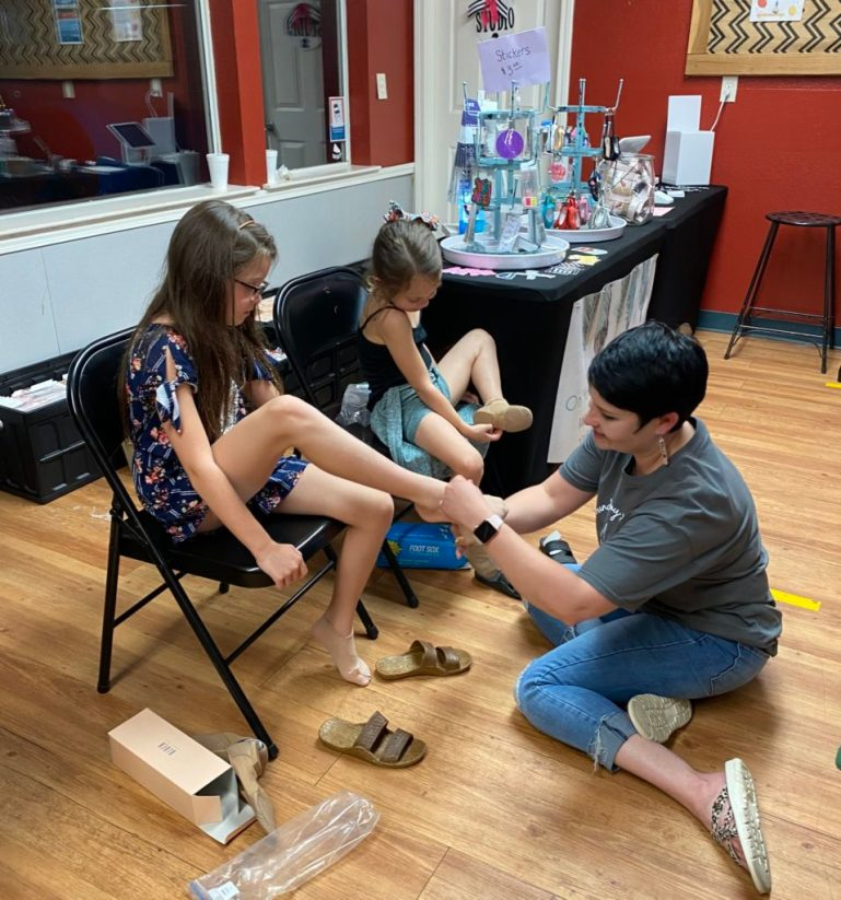 Adrienne Hansen, owner of On Your Toes Performance Wear, fitting two young girls with dance shoes at Kathryn's Dance Company.
