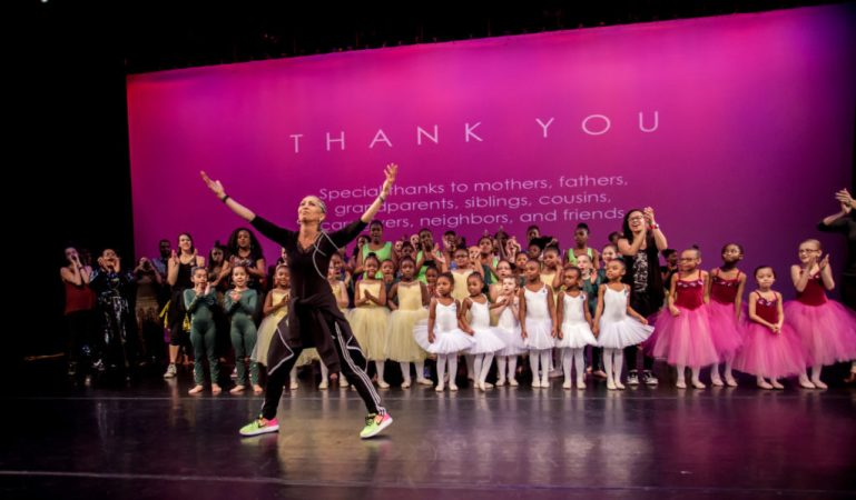 """Cynthia King stands at the front of the stage, arms outstretched overhead, at the end of a recital. Her students, in various costumes, stand behind her, and a projection on the back of the stage has a """"thank you"""" message."""