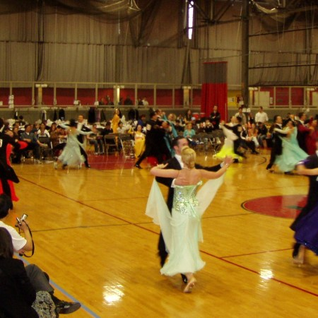Ballroom dance competition with judges.