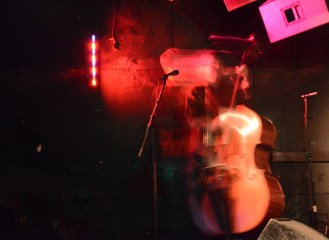 Bassist Brian Vandemark blurs across the stage during a performance with Hovering Breadcat, one of the four bands to perform at the Bluegrass & Beyond Extravaganza at Milk Bar on Haight Street in San Francisco, Ca. on Sunday, July 31, 2016. Photo by David Andrews.