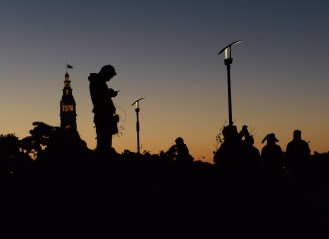 """Marc DeLeon, left, plays Pokemon Go on his phone as other players, including one in a Pikachu hat, walk by him in Rincon Park in San Francisco, Ca. on Tuesday, July 20, 2016. An estimated 9,000+ """"trainers"""" attended the Pokemon Go crawl along the city's eastern piers of Embarcadero, which featured lures at frequently-placed PokeStops, abundant rare Pokemon and food and drink specials from nearby establishments. Photo by David Andrews."""