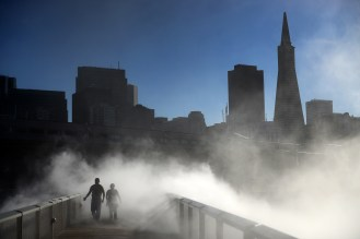 Isaac Castaneda, left, and Liz Chan walk across the fog bridge between piers 15 and 17 at the Exploratorium in the Embarcadero in San Francisco, Ca. on Tuesday, October 18, 2016. Designed as a free exhibit to the public in 2013 by artist Fujiko Nakaya, the fog bridge dispenses desalinated, recycled bay water every two hours from 12 p.m. - 6 p.m. for only about five minutes to ensure large quantities of water aren't wasted during the ongoing drought. Photo by David Andrews.