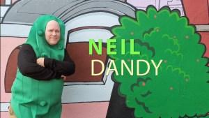 Neil Dandy posing in a pickle suit