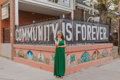"""Toronto-Danforth candidate Maryem Tollar in front of a banner reading """"Community is forever""""."""
