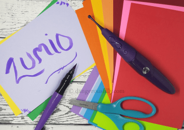Zumio Classic Review - Zumio shown on top of multi-colored papers with craft scissors and a paint marker