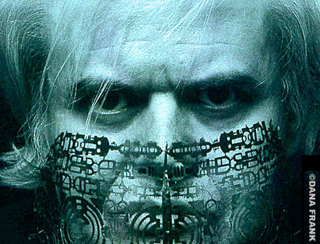 An image of HR Giger in blue tones with his own art projected onto the lower half of his face