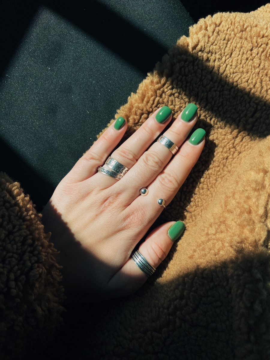 person wearing silver ring with green manicure