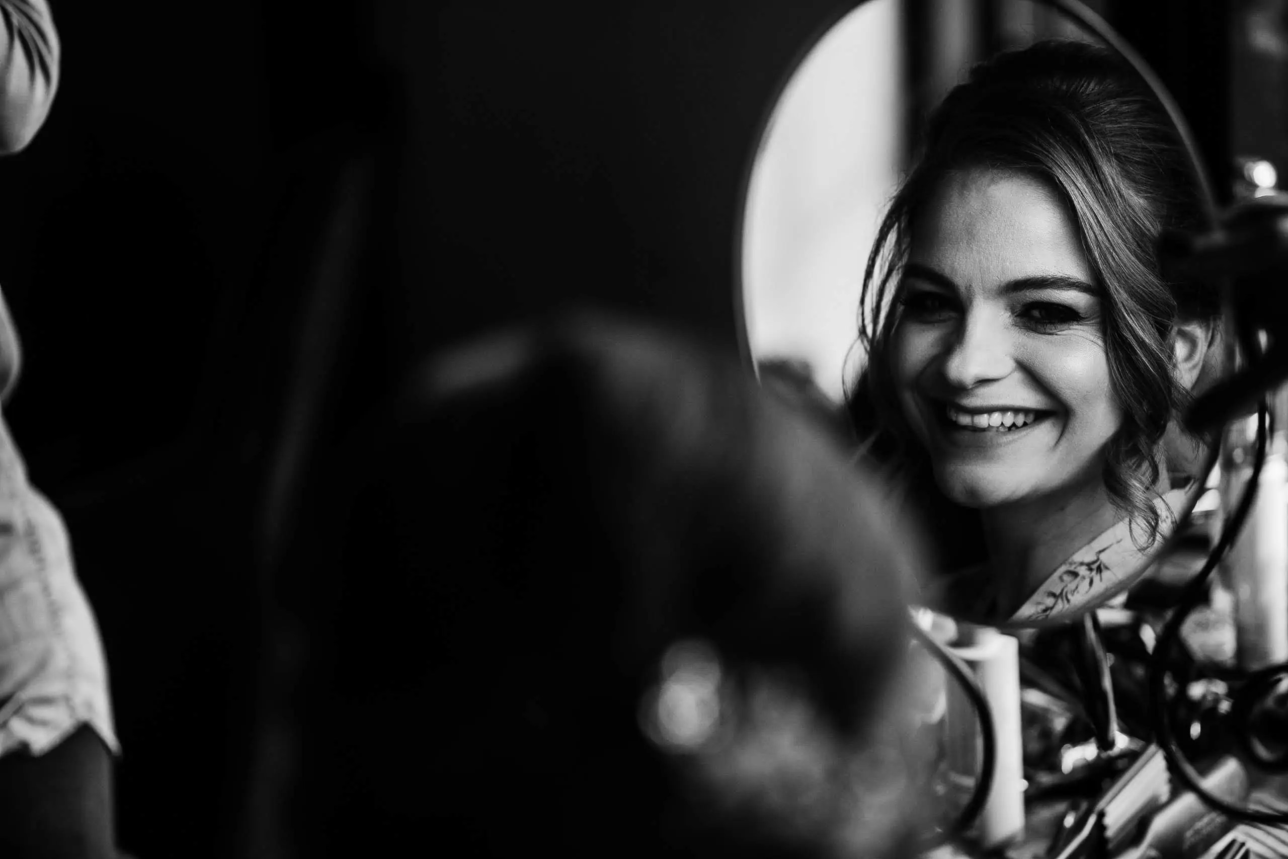A bridesmaid is smiling into a mirror as she is having her hair and makeup done at Botley Hill Barn