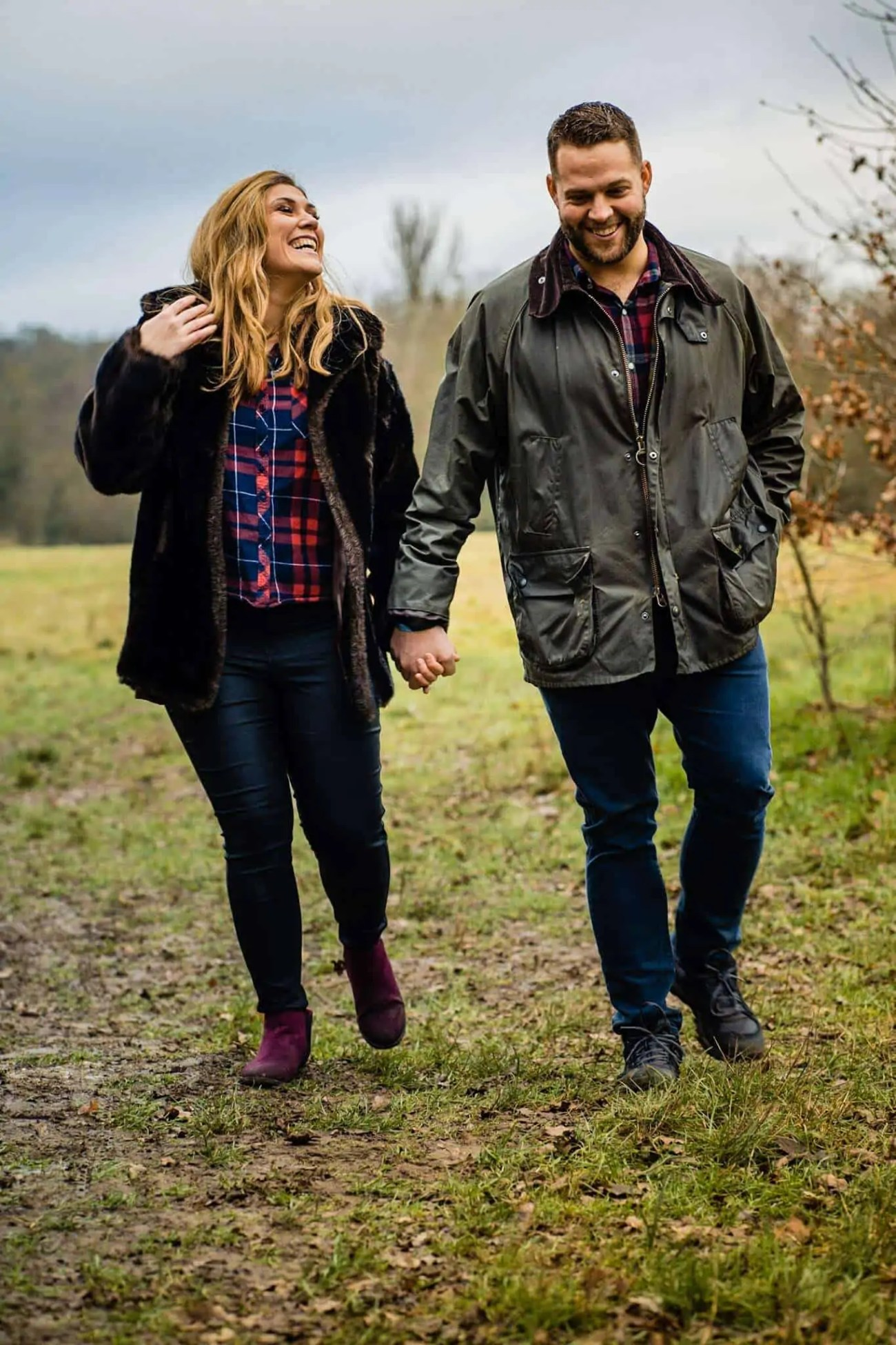 An engaged couple walking through a park in north London holding hands