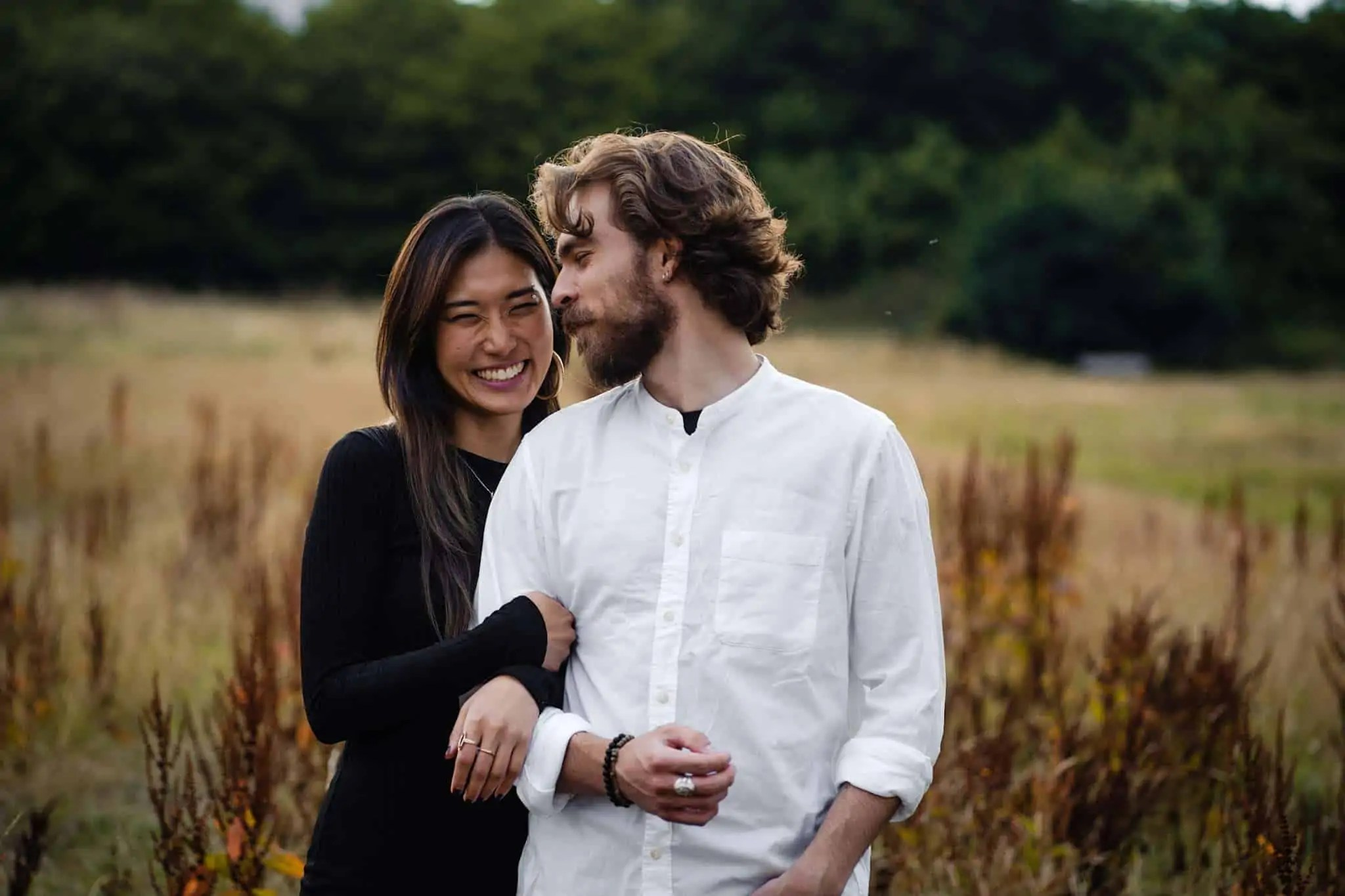 An engaged couple laughing during an engagement shoot on Hampstead Heath