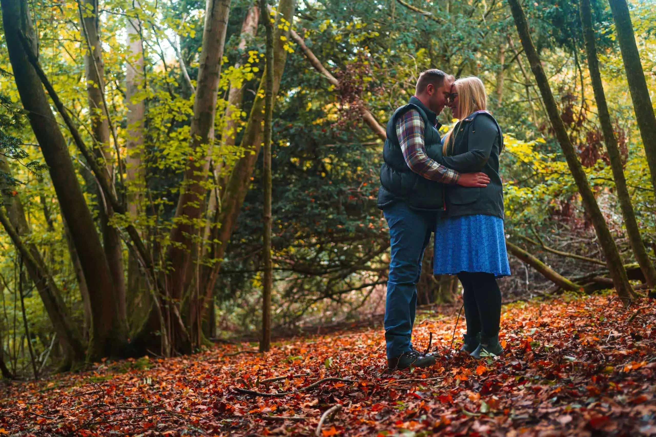 An engaged couple share an embrace in woodlands