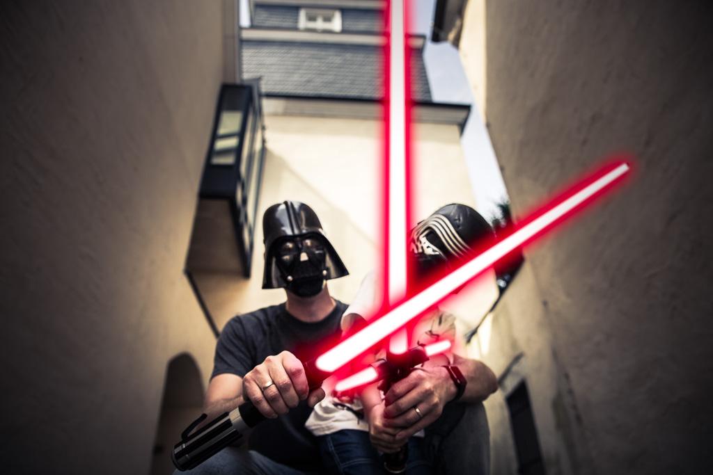 Vater und Sohn mit Star Wars Equipment und leuchtenden Lichtschwertern beim Familienshooting