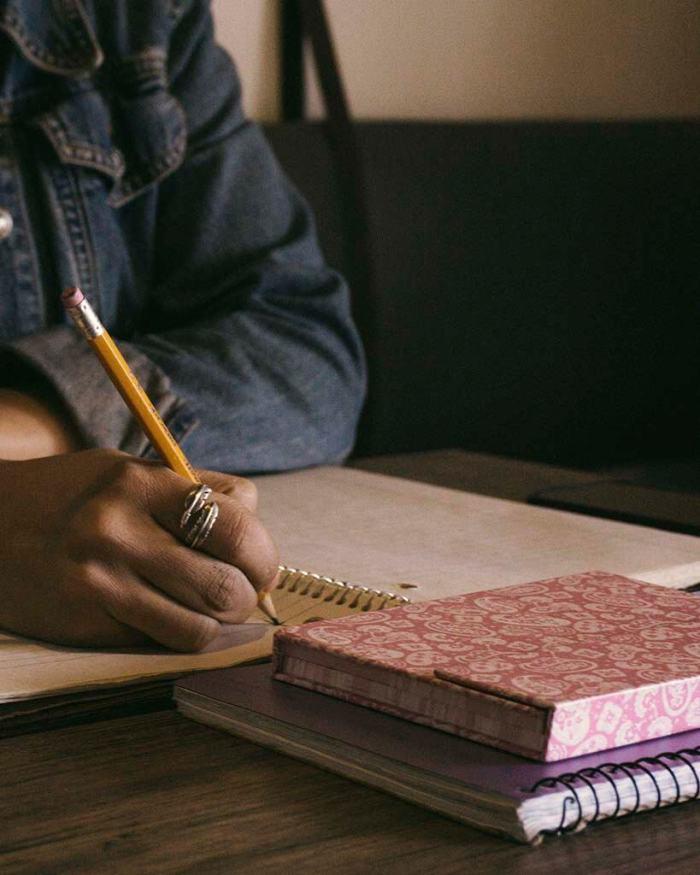 mulher escrevendo com lápis