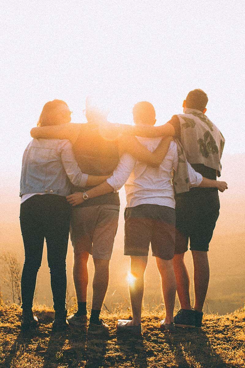 quatro amigos reunidos, com roupa informais,  admirando o pôr do sol