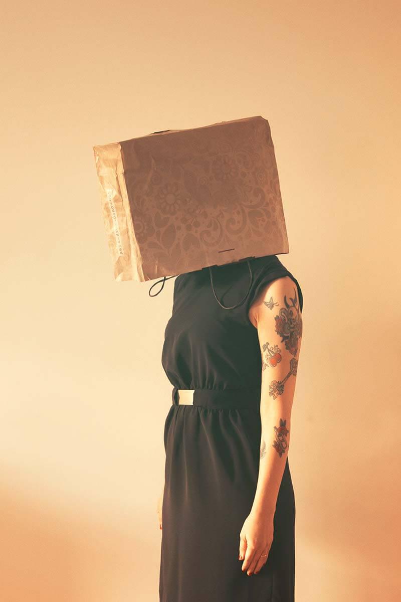 Mulher com uma caixa de papelão na cabeça