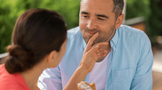 Foto de um homem e uma mulher juntos. A mulher coloca uma das mãos na boca do homem.