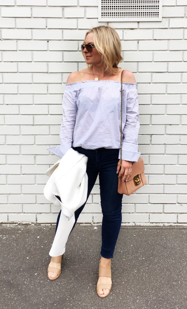 lady standing infront of a white wall wearing dark denim jeans and striped off the shoulder top holding white jacket and chloe elsie handbag