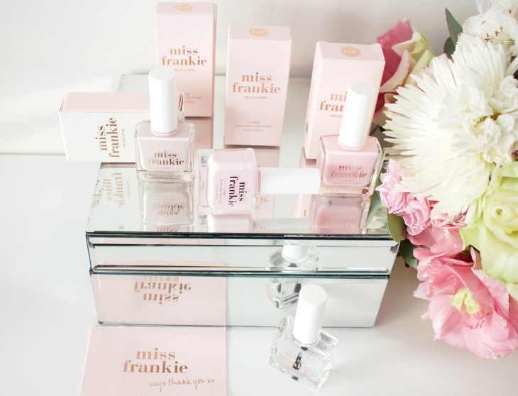 miss frankie nail polish packaged in pale pink box placed on a mirrored box next to fresh flowers