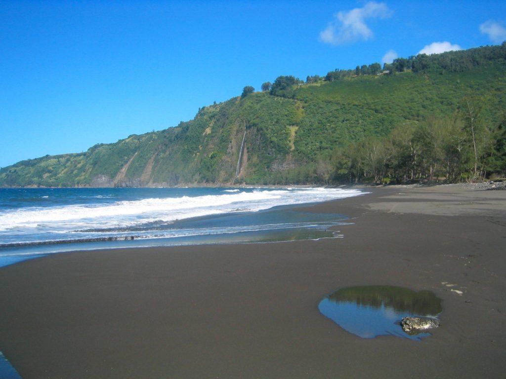 The black sand beach touches Waipio Bay.
