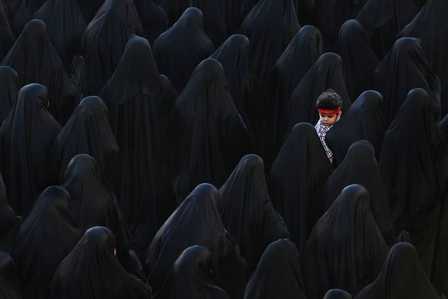 A Bahraini Muslim woman carrying her son while taking part in the funeral of Isa Radhi, the Bahraini protester who was allegedly killed during Martial Law in Sitra Village, South Manama on March 22, 2011.