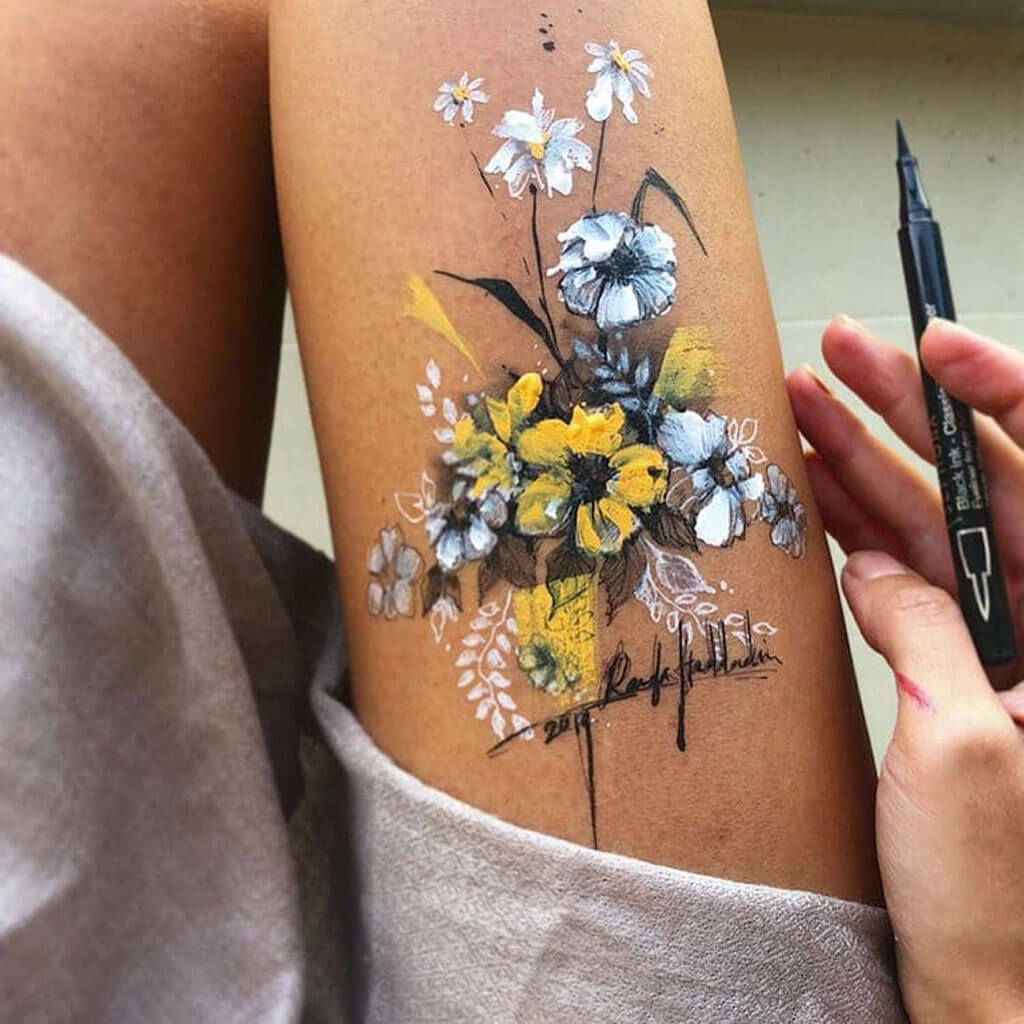 Drawing floral patterns on her thigh