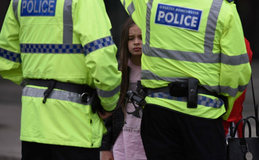 A woman and a young girl wearing a t-shirt of US singer Ariana Grande talks to police near Manchester Arena following a deadly terror attack in Manchester, northwest England on May 23, 2017. (AFP PHOTO / Oli SCARFF)