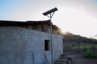 A solar panel on the López family home draws from the fading sun to store energy to power the home at night on March 9, 2015 in Sabana Grande, Nicaragua. The panel can power four lightbulbs at night and play music or charge a cellphone during the day. Danika Worthington/JMC 470