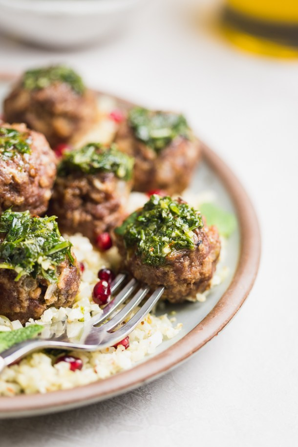 Close up of garlic meatballs topped with chimichurri.