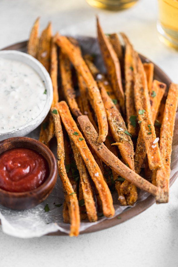 Sideview close up of crispy sweet potato fries and ranch and ketchup dipping sauces.