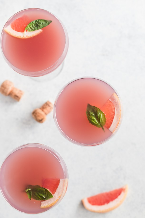 Overhead shot of 3 coupe glasses filled with a pretty pink cocktail made with gin, rose, and grapefruit juice.