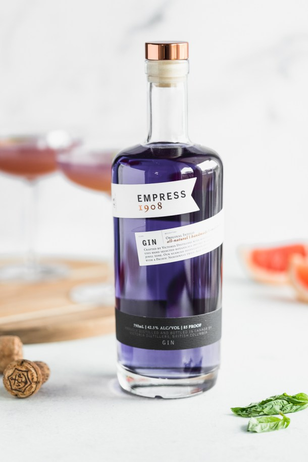A bottle of empress 1908 gin with cocktails and grapefruit in the background.