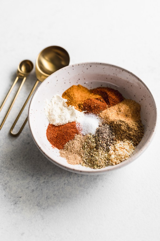 A side angle shot of a bowl of a spice blend of chili powder, cumin, garlic powder, onion powder, dried oregano, smoked paprika, dried coriander, and salt and pepper with 2 gold measuring spoons.