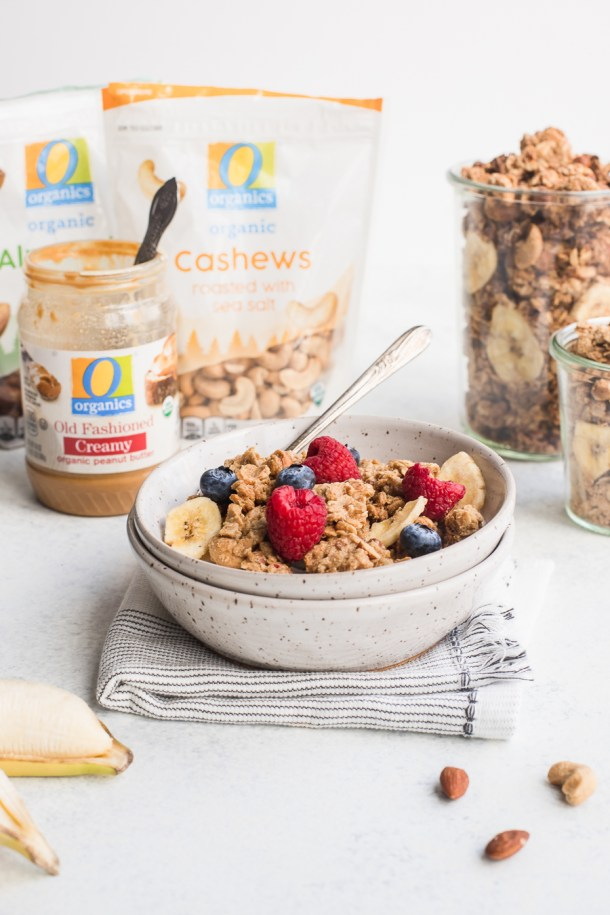 A bowl of granola flavored with banana chips and peanut butter and a 2 jars of granola in the background.