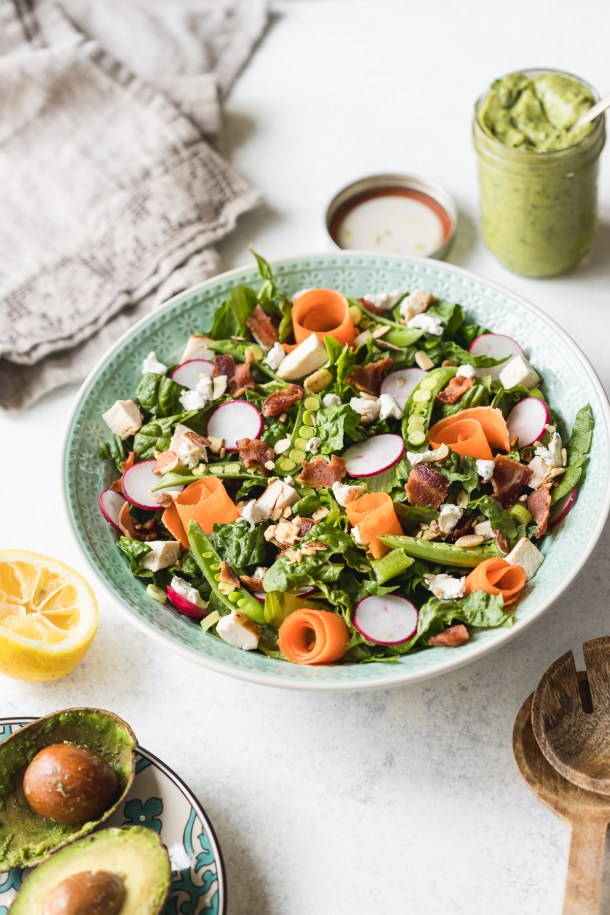 A aqua salad bowl filled with romaine lettuce, carrot ribbons, chicken, bacon, herb cream cheese, radishes, snap peas, and almonds. A napkin and container of avocado green goddess dressing in the back.