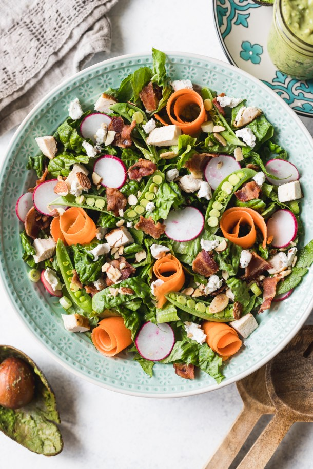 A close up overhead shot of an aqua salad bowl filled with romaine lettuce, carrot ribbons, chicken, bacon, herb cream cheese, radishes, snap peas, and almonds.