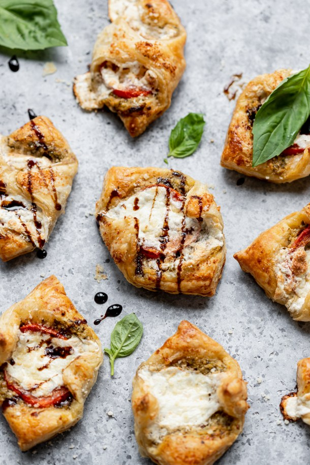 side shot of puff pastry topped with Roma tomatoes, fresh mozzarella, homemade pesto and baked to golden brown perfection. Drizzle with balsamic glaze.