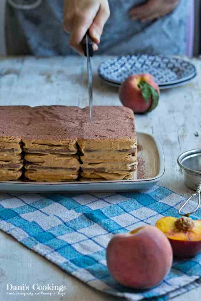 Easy icebox cake with Dulce de Leche on a serving plate being cut with a knife. Peaches are placed around it
